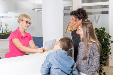 Woman with two Kids at the Dentist getting a medical appointment