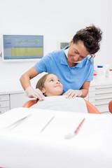 Zahnärztin beruhigt junge Patientin vor der Kontrolluntersuchung