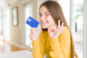 Beautiful young girl kid holding credit card doing ok sign with fingers, excellent symbol