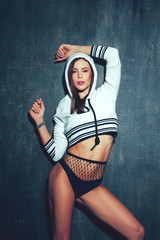 Sexy dancer woman in short pullover hoodie at night