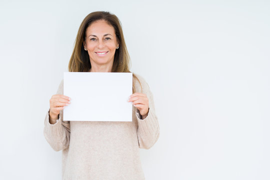 Middle age woman holding blank paper sheet over isolated background with a happy face standing and smiling with a confident smile showing teeth
