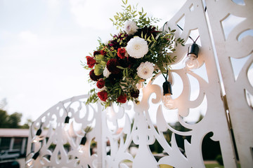 Wedding arch decorated with red flowers