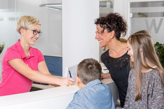 Frau mit ihren beiden Kindern am Empfangsbereich einer Arztpraxis und Sprechstundenhilfe