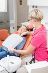 Junge bei Zahnbehandlung lächelt der Zahnarzthelferin zu