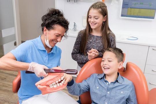Zahnärztin erklärt spielerisch zwei Kindern, dass richtige Zähneputzen