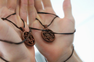 Man's hand holding a David Star or Magen David made of wood. The State of Israel, Judaism, Zionism concept image. Conversion to Judaism, giyur concept.