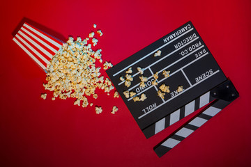 Cinema concept. Clapperboard, ticket and popcorn on red background