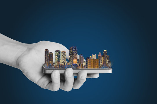 Smart city, smart building, and real estate business. Businessman hand holding mobile smart phone with modern building on blue background