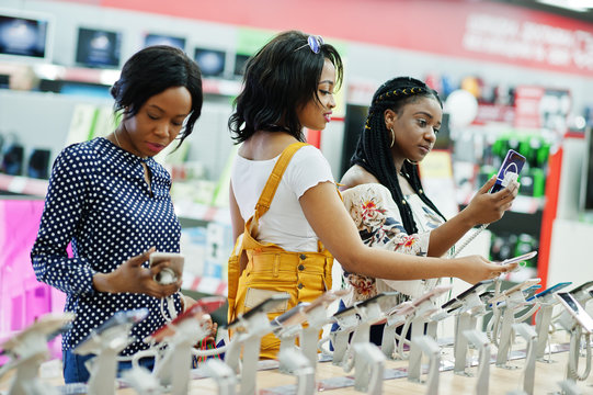 Beautiful three well-dressed afro american girls customers with colored shopping bags in mobile phone shop choosing smartphone.