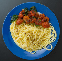 Pasta with tomatoes on blue plate
