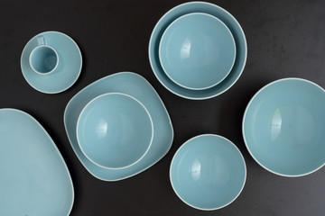 Blue empty plates on black table