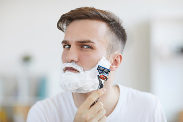Head and shoulders portrait of handsome young man shaving in morning  looking at camera, copy space