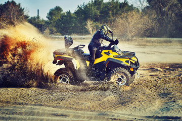 Poster Motorise Teen riding ATV in sand dunes making a turn in the sand