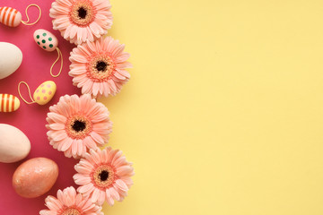 Easter flat lay in yellow and coral colors with painted eggs and gerbera daisies, copy-space
