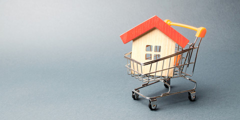 Wooden house in a Supermarket trolley. The concept of buying a house or apartment. Affordable housing. Profitable and cheap loans for real estate. Buying a home. Mortgage and loan. Place for text