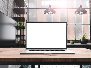 Laptop with blank screen mockup template on table in industrial old factory loft interior - front view
