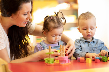 Children play with shapes and colorful wooden puzzle in a montessori classroom