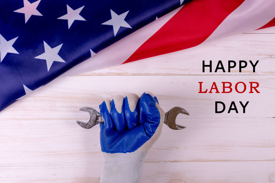 Male hand worker holding wrench, on American flag background, isolate. With an inscription, happy labour day. International celebration.