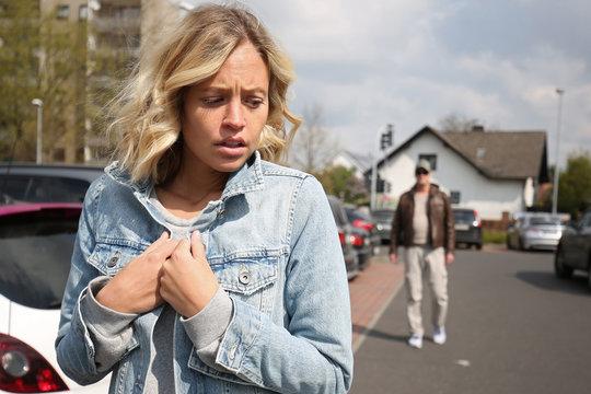 Junge Frau fühlt sich von einem Mann verfolgt