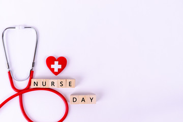 "International Nurse Day, Healthcare and medical concept.  Red heart with Stethoscope on white paper background and wooden cube text ""NURSE DAY""."