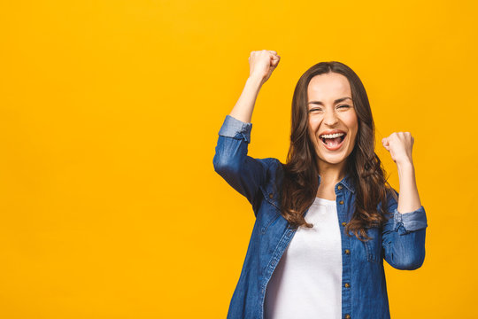 I'm winner! Happy successful young woman with raised hands shouting and celebrating success over yellow background.