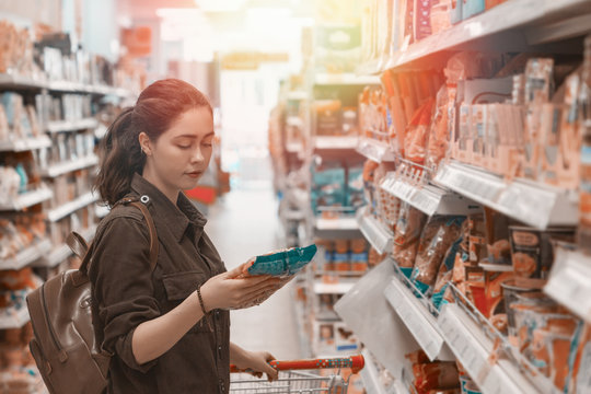 A young pretty woman holds a grocery cart and carefully chooses the products in the store. Light. Close up