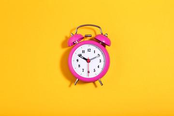 Pink alarm clock on yellow background. Minimalism concept