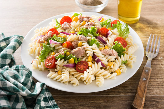 Pasta salad with vegetables and tuna on wooden table