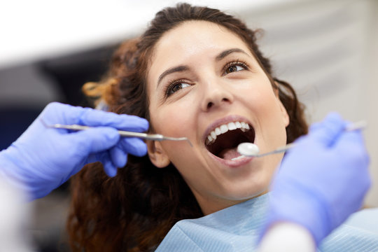 Head and shoulders portrait of beautiful young woman lying in dental chair with mouth open during consultation, copy space
