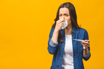 Young woman having flue taking thermometer. Isolated against yellow background. Beautiful young woman is sick with a high temperature, a thermometer, isolated close-up. Cold, flu concept.