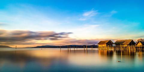 Das Pfahlbautenmuseum am Bodenseeim Sonnenuntergang mit bunter Wolkenstimmung  Fototapete