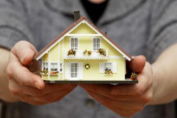 Hände halten ein Haus