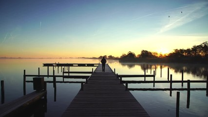Fotomurales - Man walking on a jetty and enjoying a tranquil sunrise at a lake.