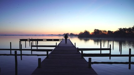Fotomurales - Man walking on a jetty and enjoying a tranquil dawn at a lake.