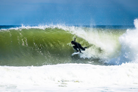 Surfer getting barreled on a sunny day surfing in Cape Cod
