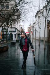 attractive man holding an umbrella while standing on the street