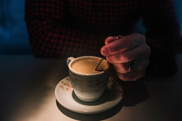 man's hands holding a cup of coffee