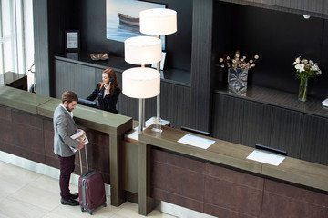 Female receptionist talking on telephone while businessman with luggage standing at hotel reception desk