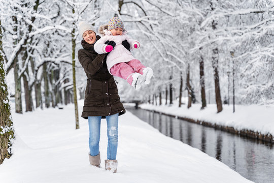 Happy mother playing with daughter in winter landscape