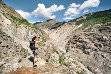 Switzerland, Valais, woman taking picture during a hiking trip in the mountains at Aletsch Glacier