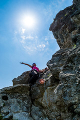Joyful young woman waving her hand up in the air after passing a difficult section on a via ferrata route in Baia de Fier, Gorj county, Romania, on the rock wall above Women's Cave (Pestera Muierilor)