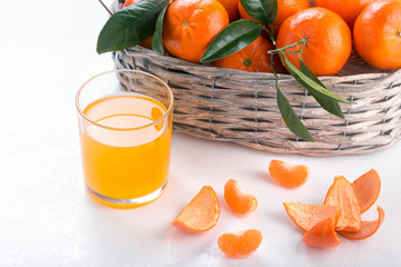 Full basket of mandarin with a glass of juice