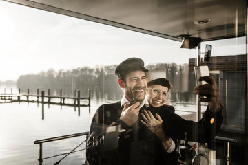 Colleagues working on a houseboat, taking selfies as sailor and captain