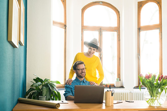 Casual entrepreneur couple in home office working at laptop and smiling