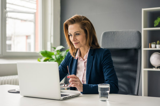 Businesswoman sitting in office, working on laptop