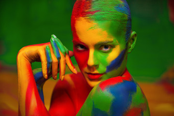 Fashion portrait of beautiful girl with bright,colorful, creative art make-up, abstract face art on colors background