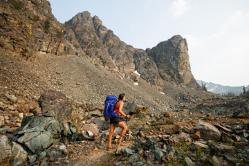 A female backpacker hiking along the trail in the Seven Devils Mountains, Idaho.