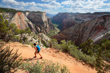A female hiker hiking along the Observation Point Trail in Zion National Park, Utah.