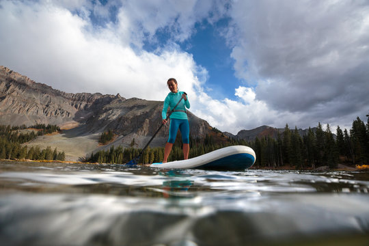 A woman paddle boards on an inflatable SUP at Alta Lakes near Telluride, Colorado in autumn in the San Juan Mountains.