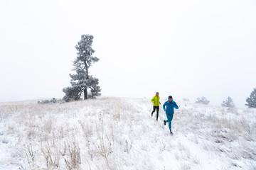Woman and man running in winter, Idaho